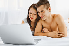Couple looking at laptop. Young beautiful couple looking at laptop while lying on the bed in their bedroom. Communication technology Royalty Free Stock Images