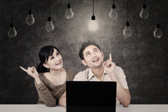 Couple looking at light bulb on chalkboard Royalty Free Stock Image