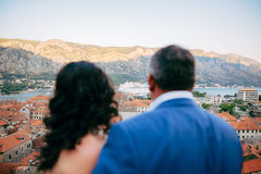 The couple is looking at the liner. The newlyweds admire the cru. Ise liner. A viewing platform on the wall above the old town of Kotor in Montenegro Royalty Free Stock Image