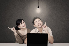 Couple looking at lit light bulb and laptop Royalty Free Stock Photography