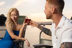Couple looking lovely on each other on the yacht, and drinking w stock photo
