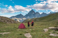 Couple looking at the majestic view of glowing mountain peaks at sunset high up on the Alps. Rear view with camping  tent, focus i Stock Photos
