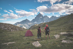 Couple looking at the majestic view of glowing mountain peaks at sunset high up on the Alps. Rear view with camping  tent, focus i Stock Image