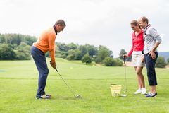 Couple looking at male coacher taking a shot. Smiling couple looking at male coacher taking a shot on golf course stock image