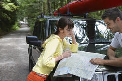 Couple Looking At Map On Car Bonnet In Forest Stock Photos