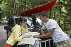 Couple Looking At Map On Car Bonnet In Forest Royalty Free Stock Photos
