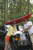 Couple Looking At Map On Car Bonnet In Forest Stock Images