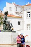 Couple pointing and statue, Lagos, Portugal. A couple looking at a map in front of the statue of Infante Dom Henrique Prince Henry in the town square with town stock photo
