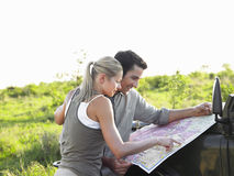 Couple Looking At Map On Jeep Bonnet At Landscape. Side view of a young couple looking at map on bonnet of jeep at landscape Stock Image