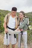 Couple looking at map on mountain terrain Stock Images