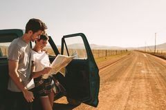 Couple on a road trip looking at map for navigation Stock Image