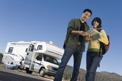Couple looking at map outside RV Royalty Free Stock Photos