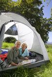 Couple looking at map in tent Stock Photos