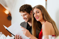 Couple looking into menu of restaurant Royalty Free Stock Photography