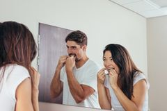 Couple using dental floss to clean their teeth. Couple looking in the mirror and smiling, using dental floss to clean their teeth. Man and women brushing teeth stock images