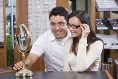 Couple Looking At Mirror While Trying On Spectacles. Happy Hispanic couple looking at mirror while trying on spectacles at shop Stock Image
