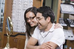 Couple Looking At Mirror While Trying On Spectacles Stock Images