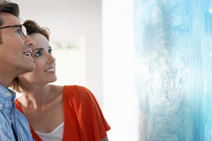 Couple Looking At Modern Art Painting. Happy couple looking at modern painting in art gallery Royalty Free Stock Image