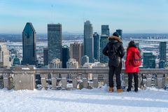 Couple looking at Montreal Skyline from ondiaronk belvedere. Montreal, Canada - 22 January 2019: Couple looking at Montreal Skyline from Kondiaronk belvedere royalty free stock photos