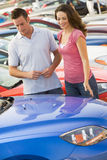 Couple looking at new cars. On lot Royalty Free Stock Images