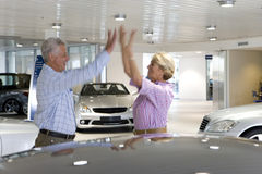 Couple looking at new cars in showroom Royalty Free Stock Photos