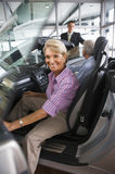 Couple looking at new convertible car in showroom, man talking to salesman, focus on woman sitting in passenger seat in foreground Stock Images