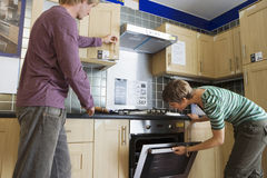 Couple looking at new kitchen in home furnishings store, man opening cupboard, woman checking oven Royalty Free Stock Photography