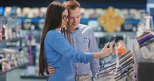 Couple looking for new smart phone to buy. Technology shopping concept. Couple looking for new smart phone to buy. Technology shopping concept stock footage