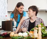 Couple looking at notebook during cooking food Royalty Free Stock Photos