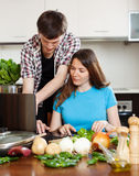 Couple looking notebook during cooking vegetables Royalty Free Stock Images