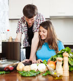 Couple looking at notebook during cooking Stock Photo
