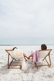 Couple looking ocean on their deck chairs Royalty Free Stock Photos