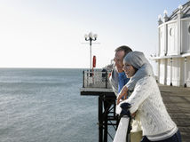 Couple Looking Out At Sea On Pier Stock Photography