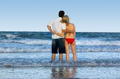 Couple looking out to sea. Couple standing at waters edge with waves crashing around them and looking out to the horizon in the late afternoon Stock Photography