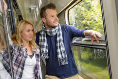 Couple looking out the train window smiling Royalty Free Stock Photos