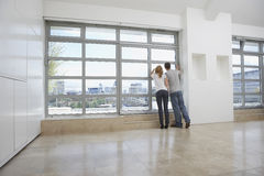 Couple Looking Out Of Window In Empty Apartment Stock Images