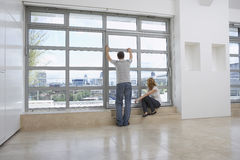 Couple Looking Out Of Window In Empty Apartment Royalty Free Stock Image