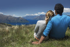 Couple Looking Over Lake And Hills. Rear view of a romantic couple looking over lake and hills Royalty Free Stock Image