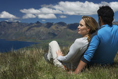 Couple Looking Over Lake And Hills Stock Photo