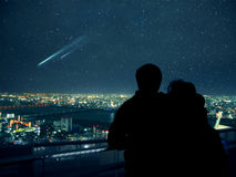Couple looking over Osaka night skyline and falling stars Royalty Free Stock Photography