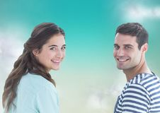 Couple looking over shoulders against blue green background with clouds Stock Photography