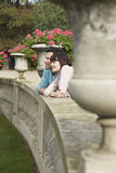 Couple Looking Over Wall By Potted Plants Stock Photography