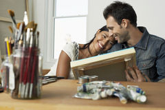 Couple Looking At Painting In Artist Studio stock images