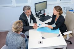 Couple looking at paperwork in meeting with businesswoman stock photos