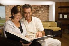 Couple looking at photo album Stock Photos