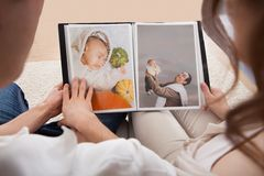 Couple looking at photo album. Portrait Of Couple Looking At Photo Album Stock Photography
