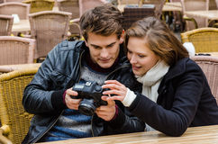 Couple Looking At Photographs On Camera At Restaurant Royalty Free Stock Photography