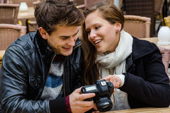 Couple Looking At Photographs On Camera At Restaurant Stock Images