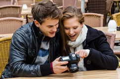 Couple Looking At Photographs On Digital Camera At Restaurant Stock Images