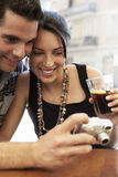 Couple Looking Photographs On Digital Camera At Sidewalk Cafe Stock Photo